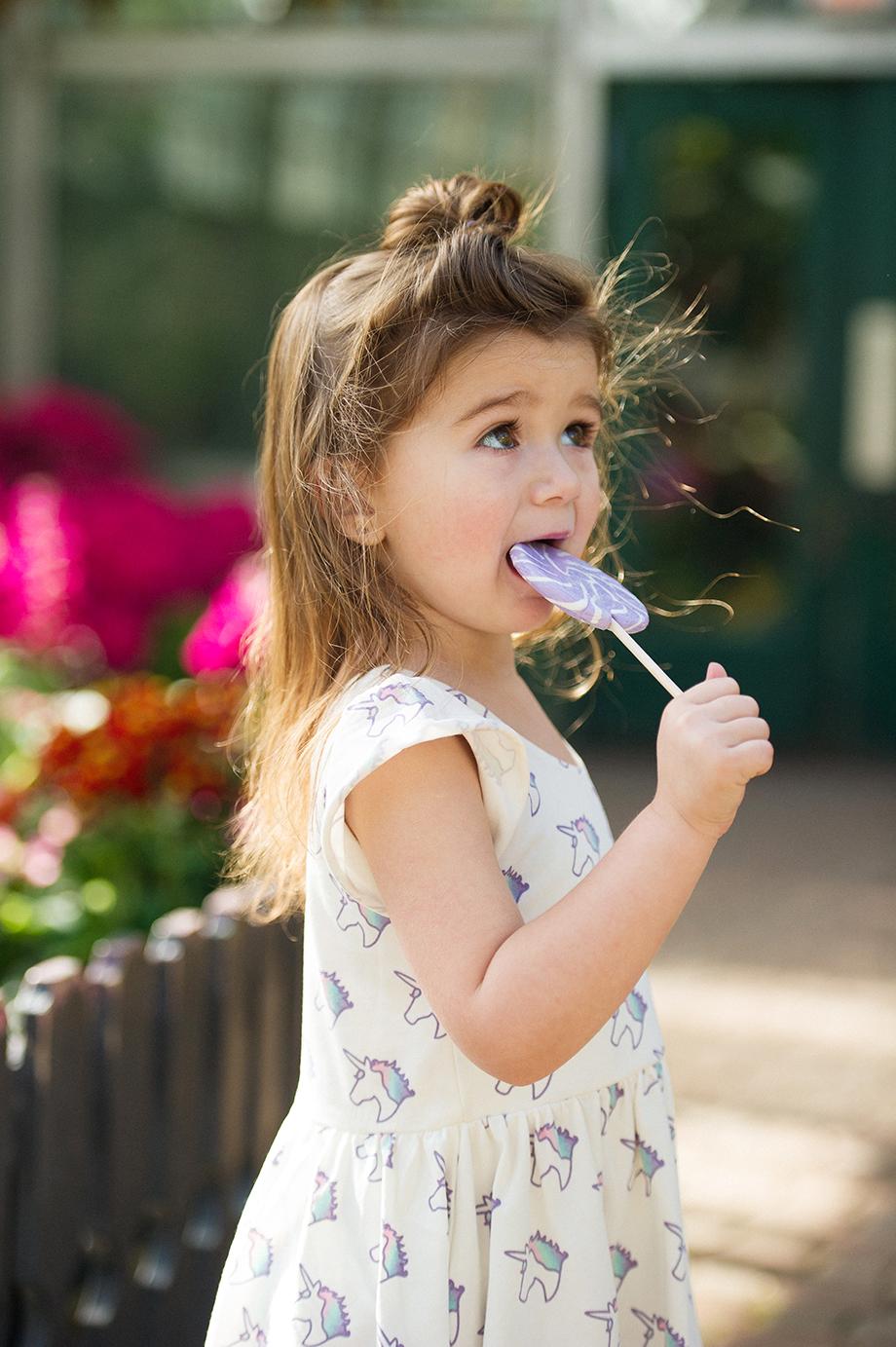 A toddler eating a purple swirl sucker in a unicorn print dress.