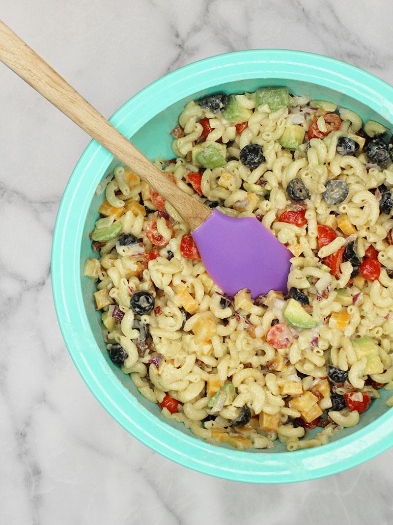 Mixing rainbow macaroni salad.