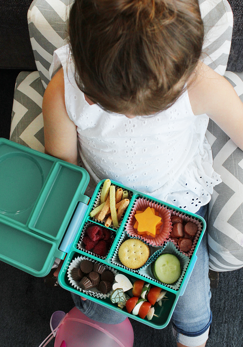 A little girl enjoys a back to school lunchables.