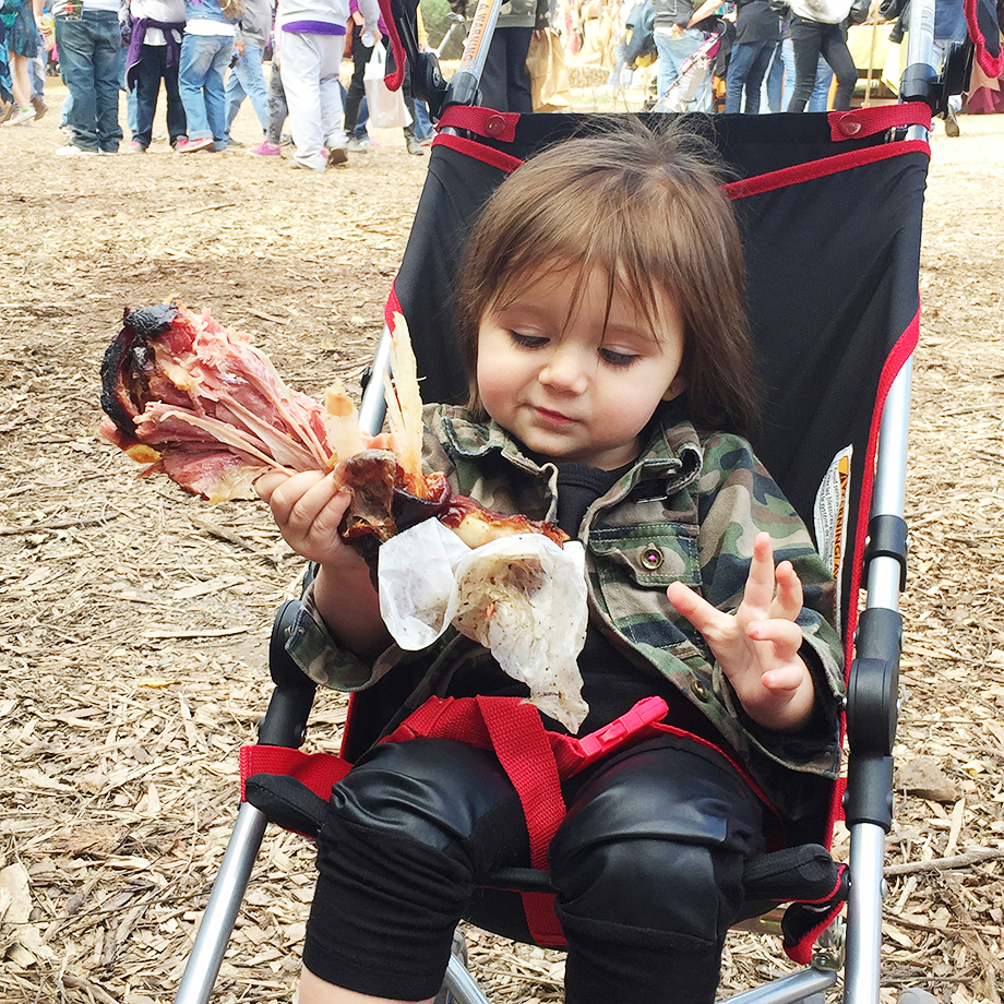 Zelda eating a large turkey leg after a road trip to Kansas City where she practiced safety tips.