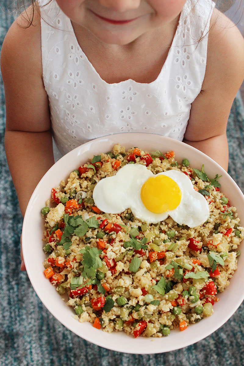 A toddler holds a bowl of cauliflower fried rice.