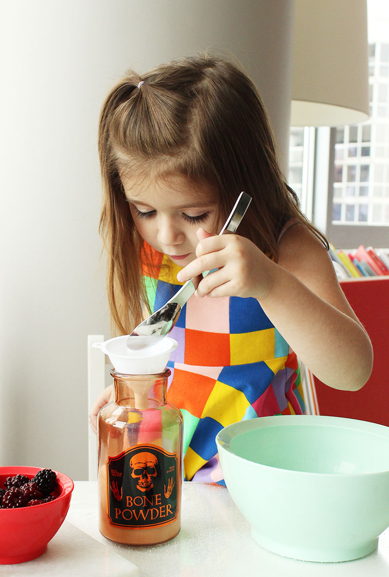 """A toddler makes """"bone powder"""" for scary witch's potion punch."""
