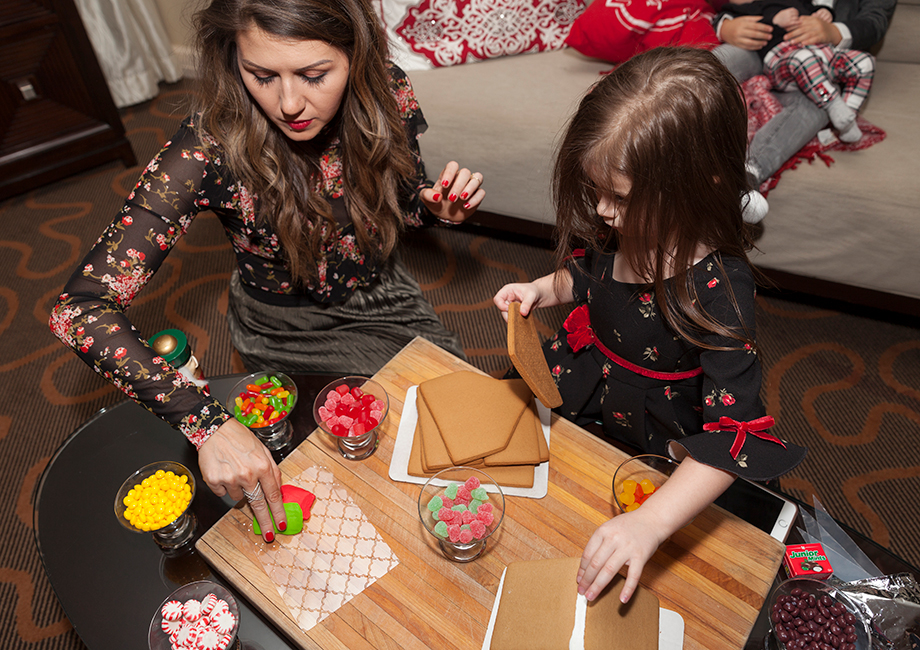 A mother and daughter build gingerbread houses at the Swissotel.