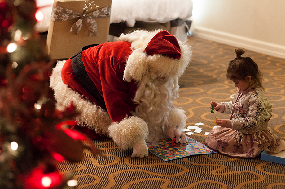Santa plays Candyland with a little girl.