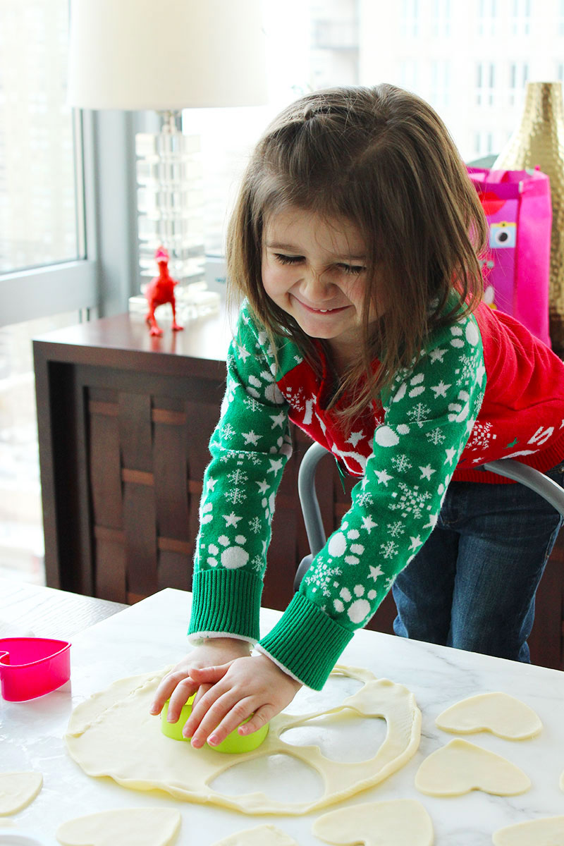 A toddler makes baked pop hearts with pie crust and jelly.