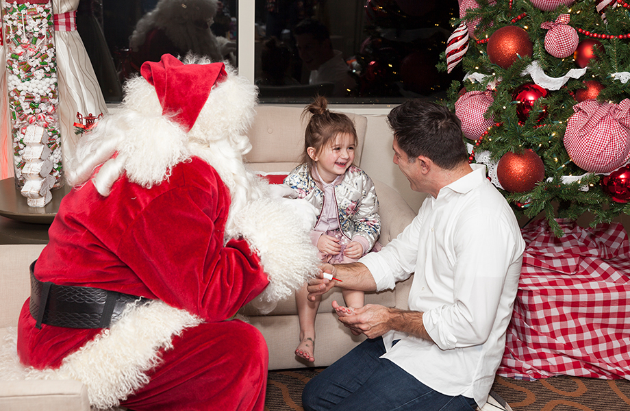 Santa gives a little girl a pedicure by a Christmas tree.