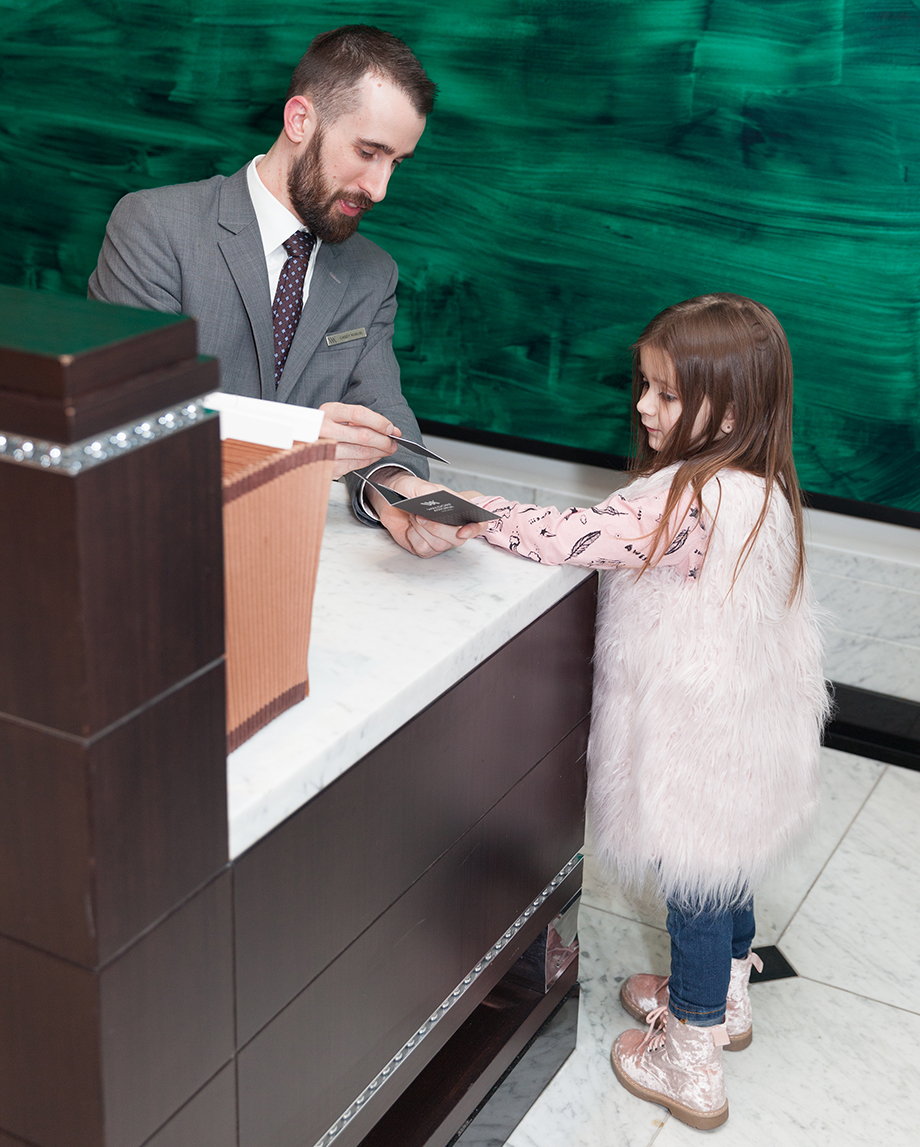 A little girl in a faux fur vest greets the front desk at the Waldorf Astoria Chicago.