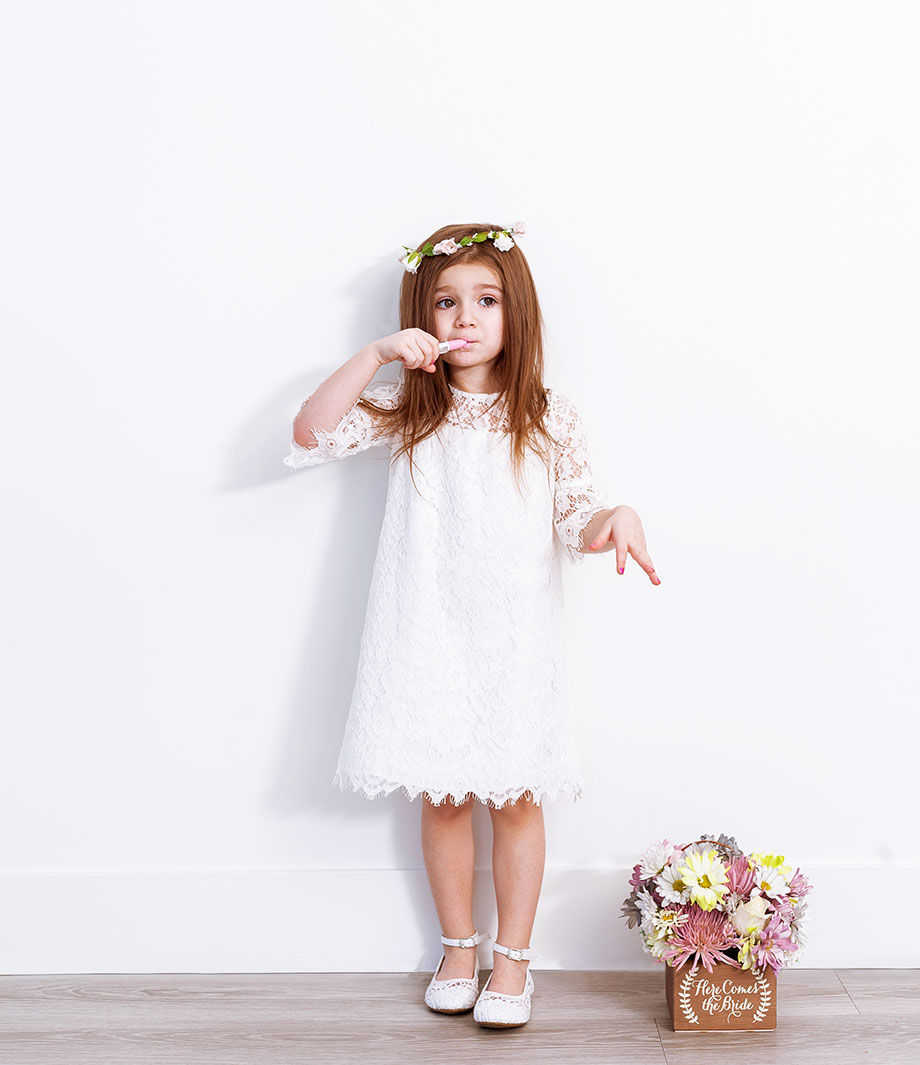A white lace flower girl dress with a flower girl basket from David's Bridal.