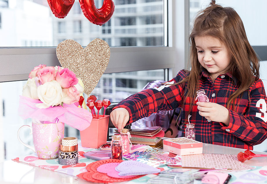 A toddler in a plaid shirt making valentines at home.