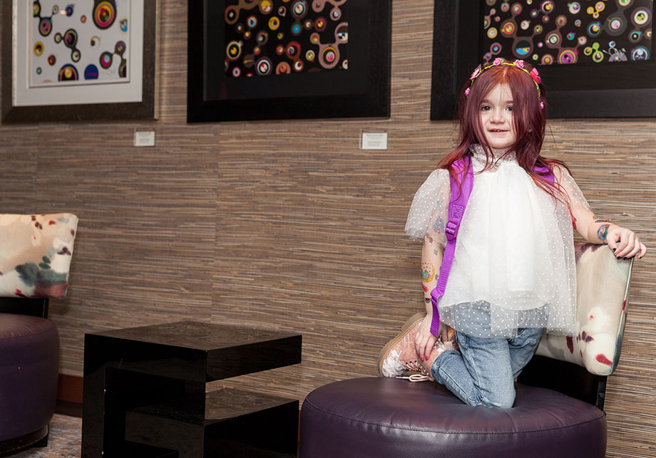 A toddler with pink hair sits on a chair at Nobu Hotel in Las Vegas.