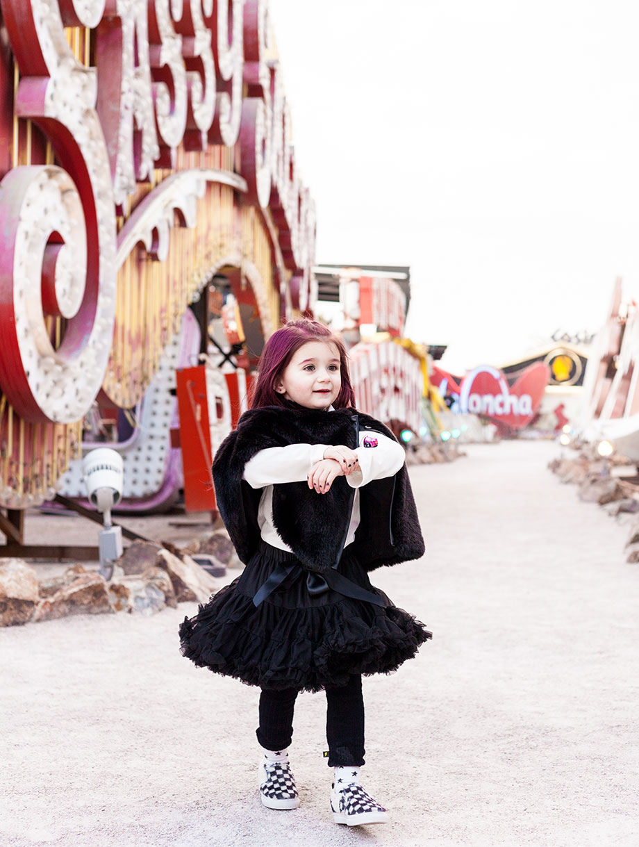 A toddler with pink hair wears a fur stole in Las Vegas.