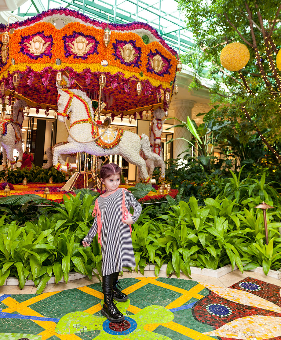 A toddler in a striped dress stands in front of florals at The Wynn in Las Vegas.