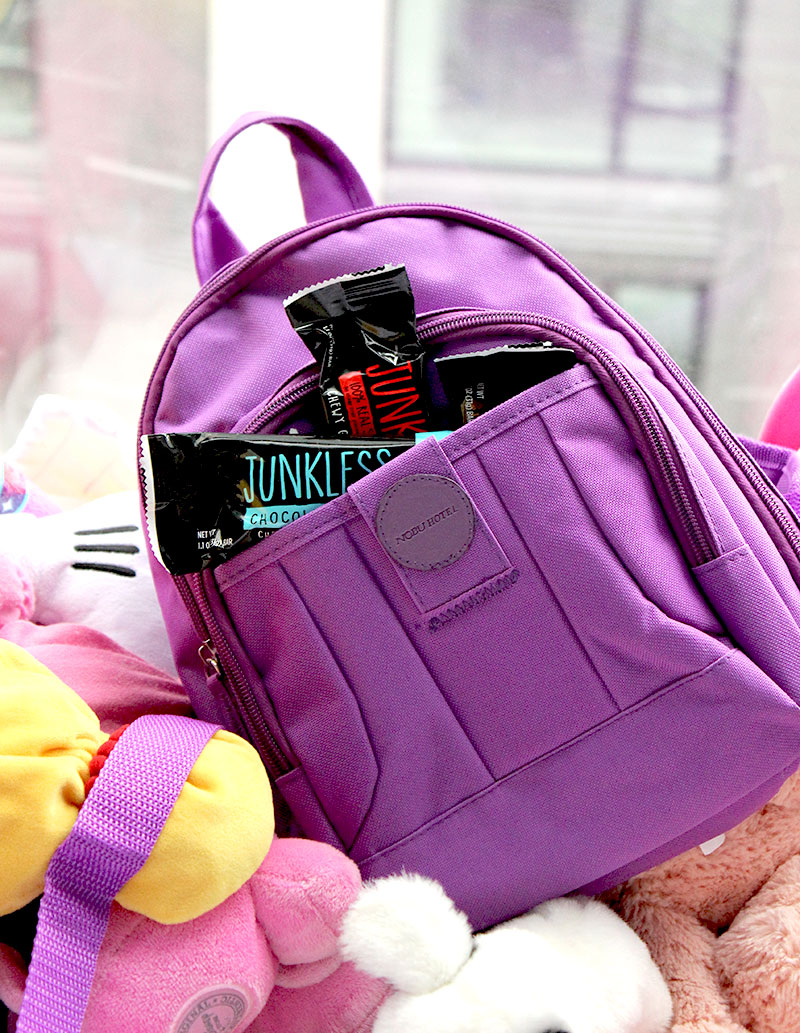 A purple backpack filled with Junkless Granola Bars on Glitter and Bubbles.