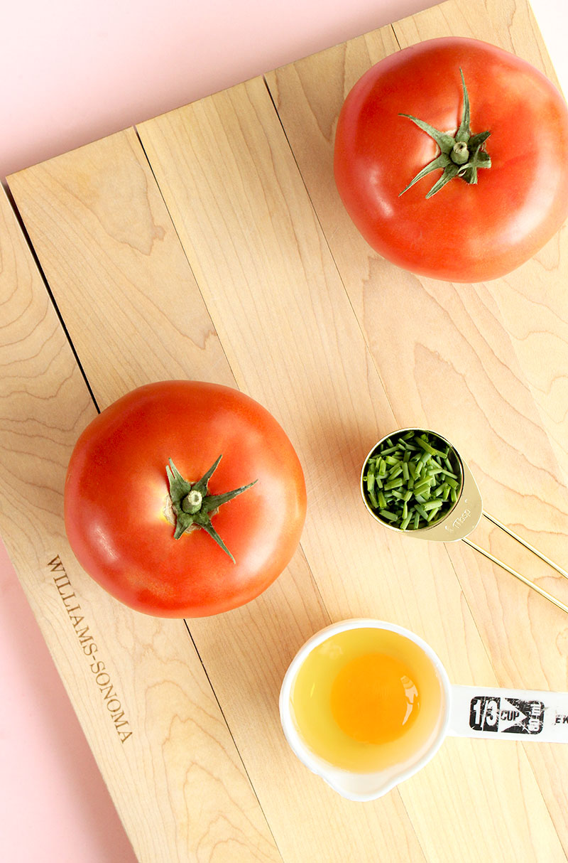 Tomatoes, chives and a raw egg sits on a cutting board from Williams-Sonoma.
