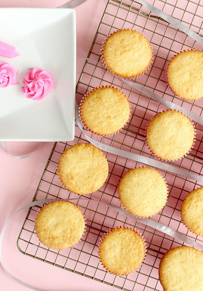 Vanilla cupcakes sit on a cooling tray.