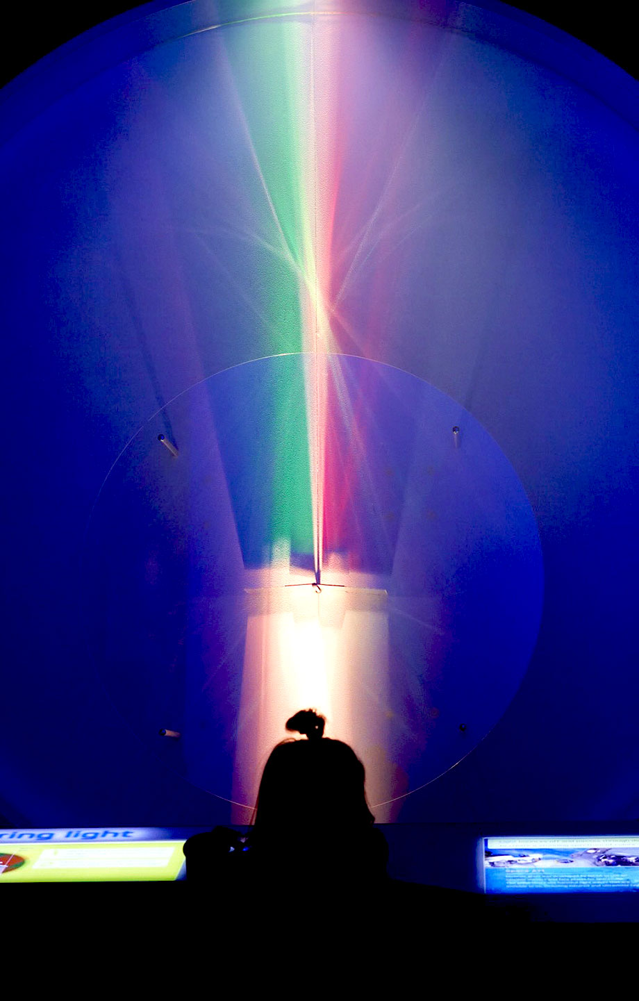 A toddler stands in front of a blue rainbow at MSI in Chicago.