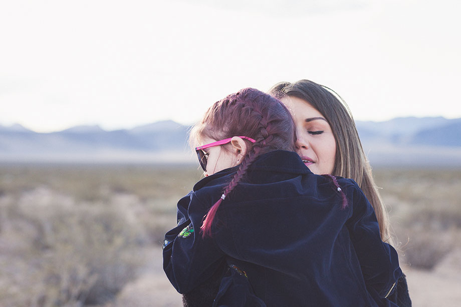 A mother and daughter hug while standing in the Las Vegas desert.