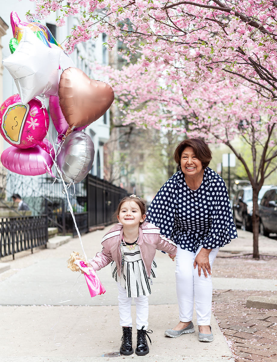 A little girl wearing pink holds a bundle of balloons outside in Chicago.