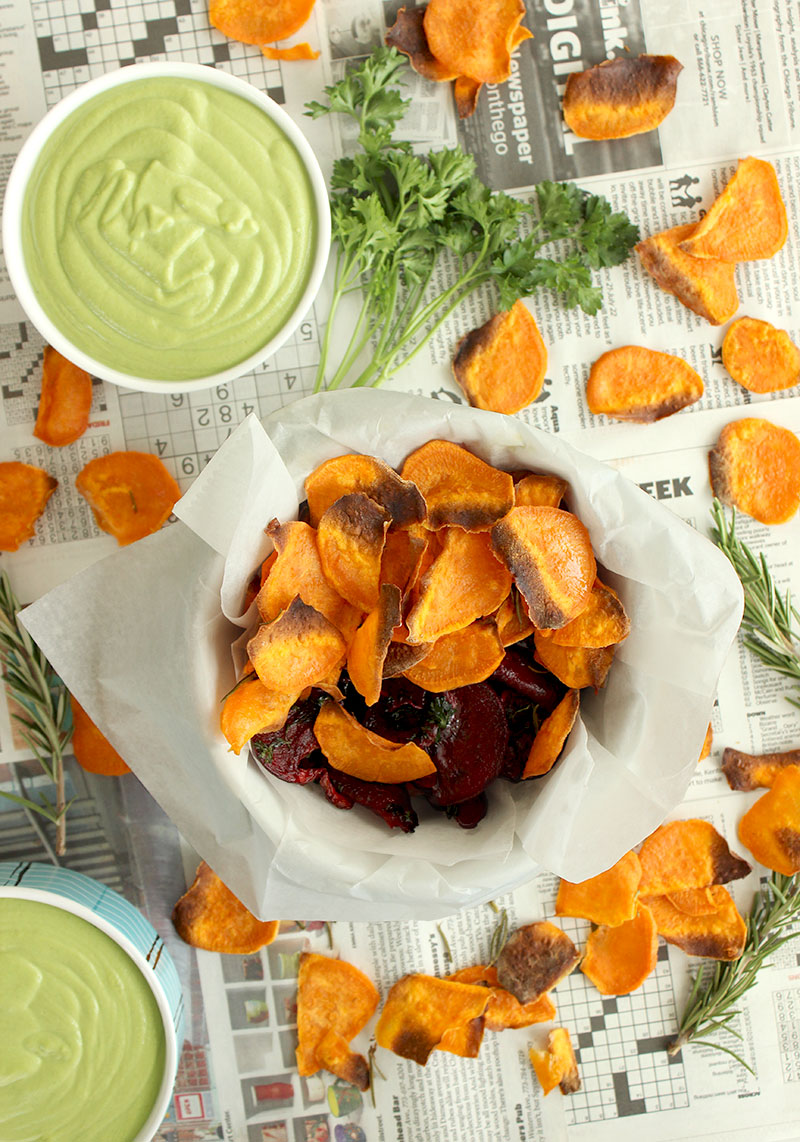 Sweet potato chips sit on newspaper with sweet pea mint dip.
