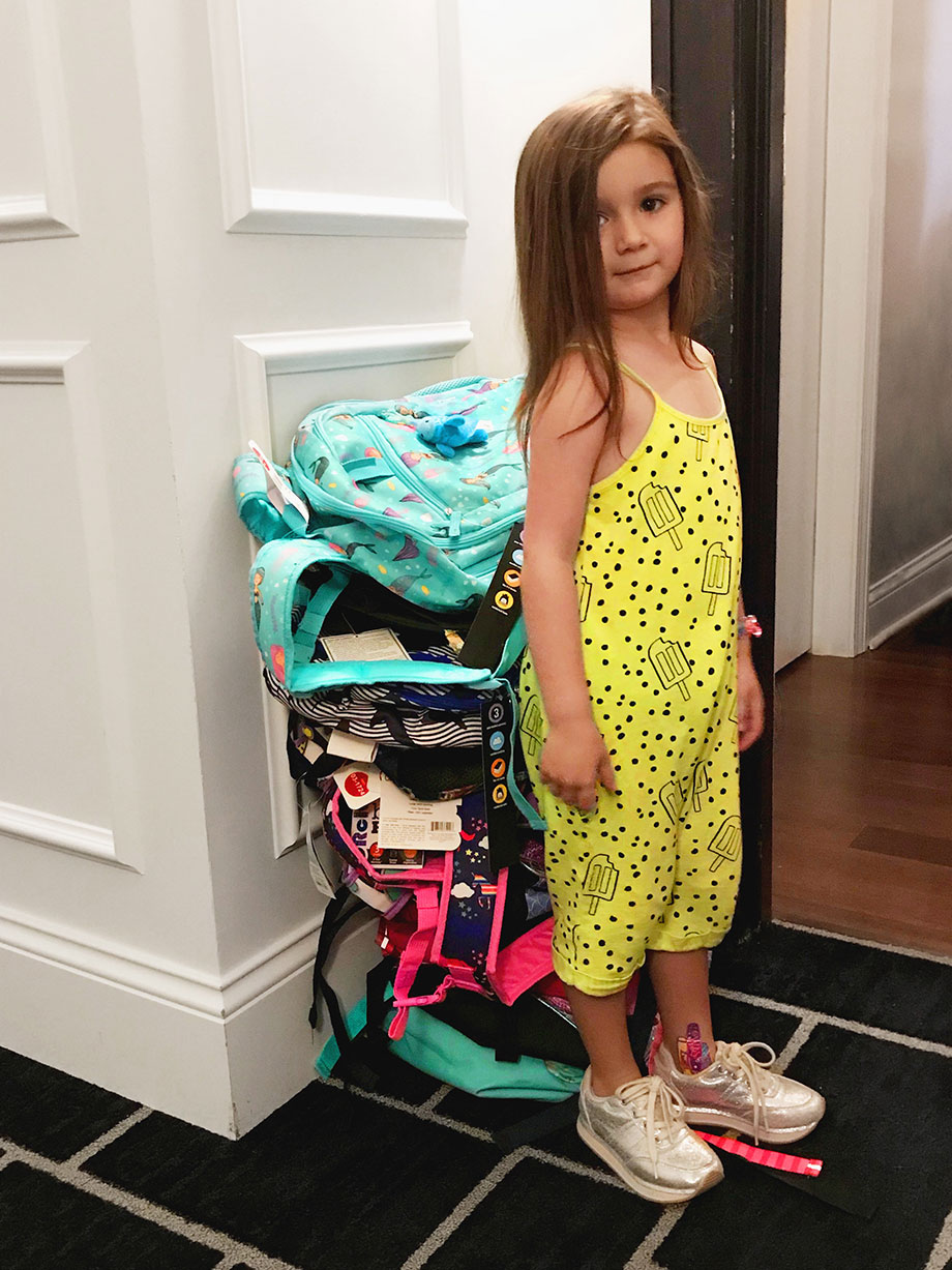 Zelda of Glitter and Bubbles stands with backpacks for the kids of Englewood's Youth.