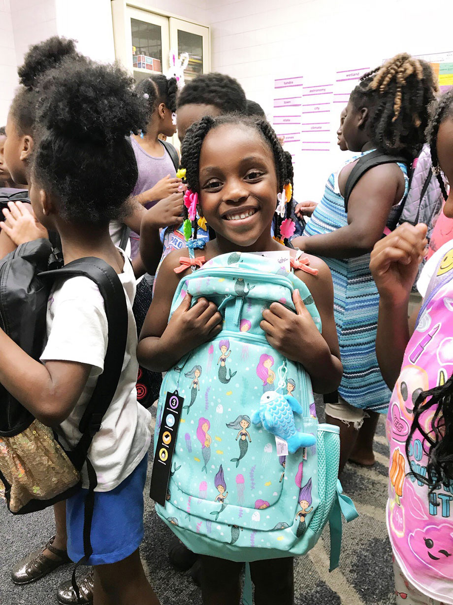A little girl at the Youth of Englewood holds a backpack.