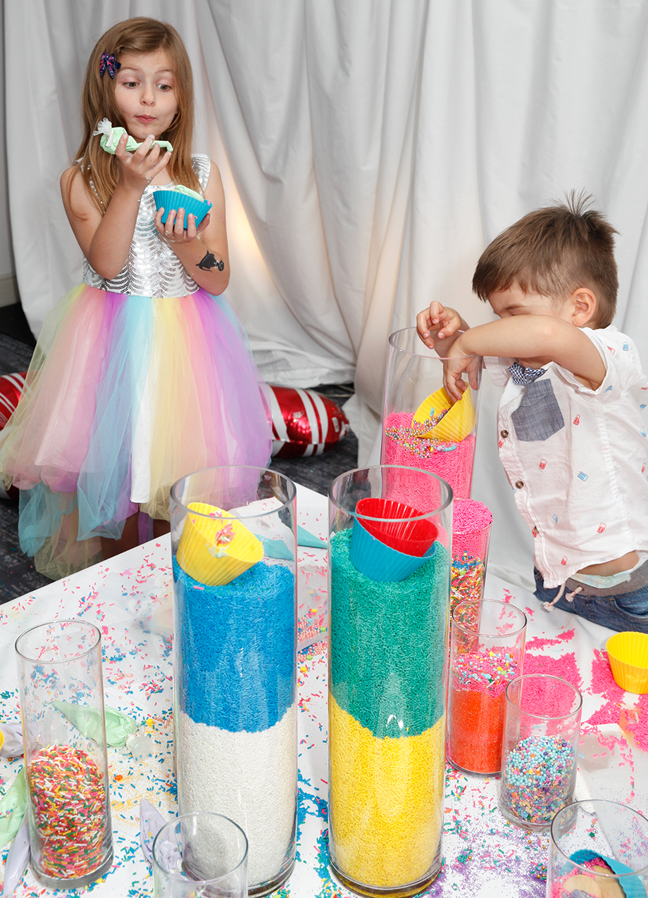 Two children decorate cookies with a giant sprinkle tower.