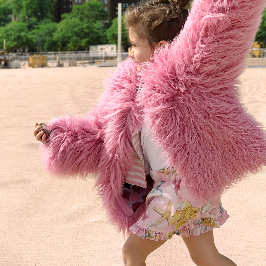 Zelda wears a pink fur coat on the beach on Glitter and Bubbles.