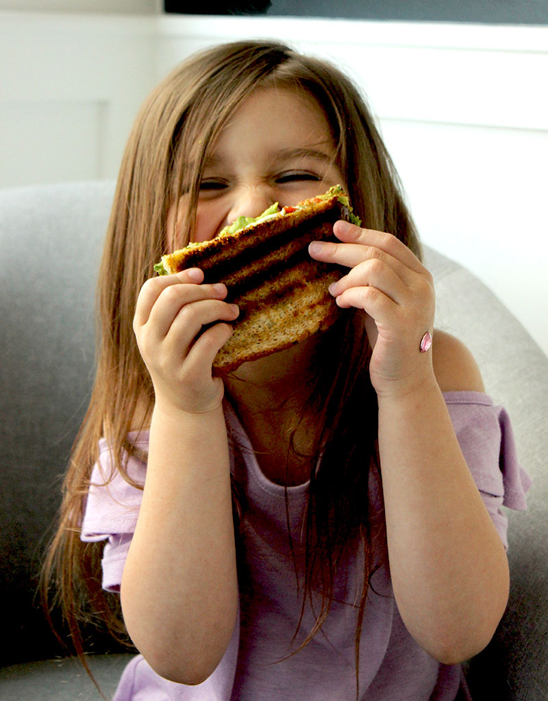 Zelda of Glitter and Bubbles holds a grilled sandwich.