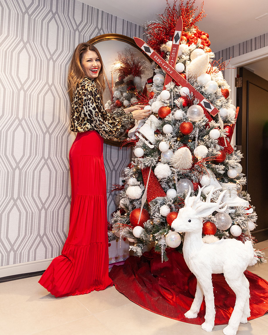 Corri McFadden stands by a Christmas Tree.