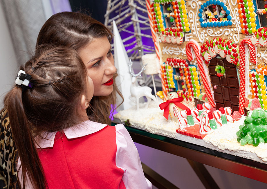 Corri and Zelda look at the Gingerbread House for Christmas.