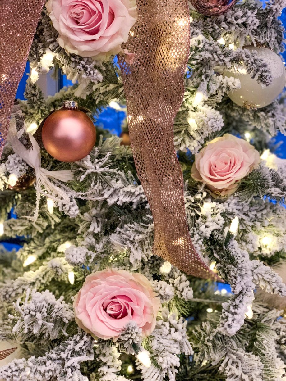 A Christmas tree filled with pink roses and ribbons.