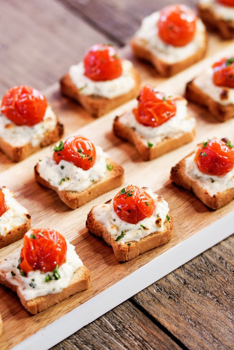 Alouette Cheese on top of tiny toasts with tomatoes.