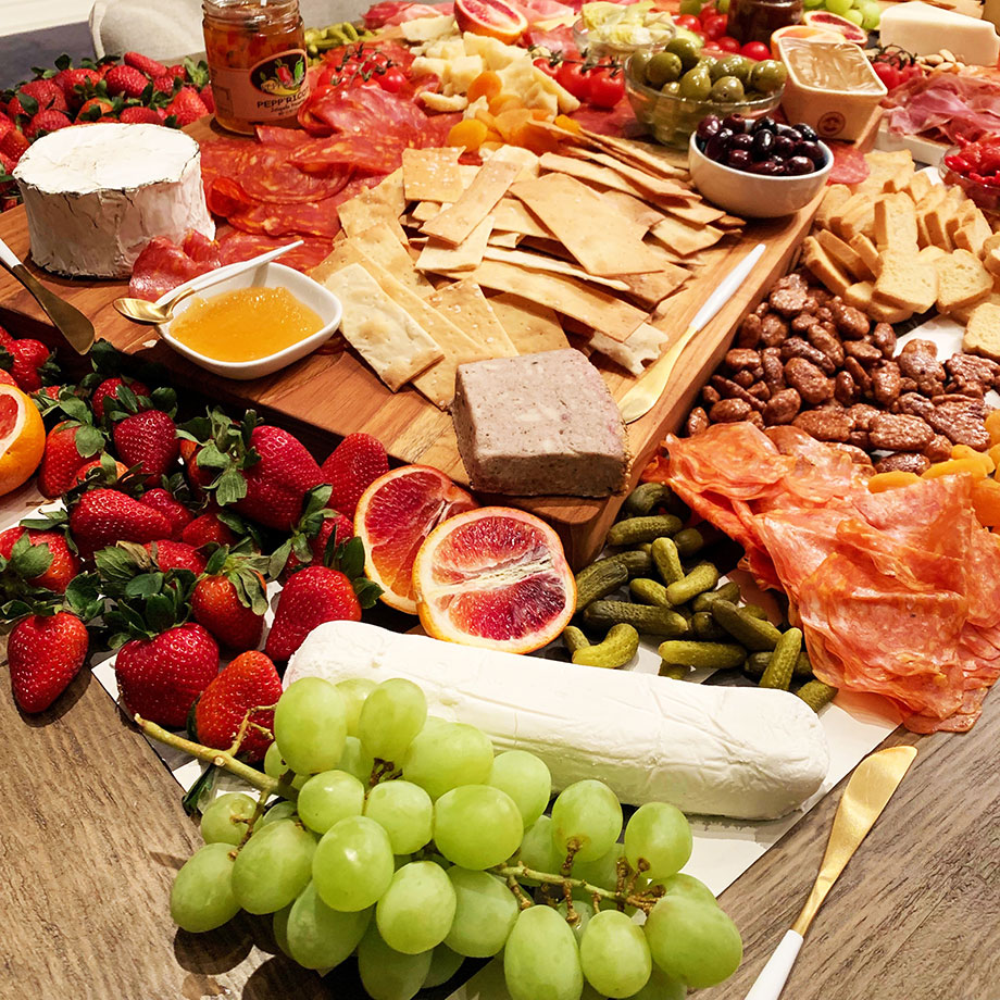 A table is filled with meat, cheese, and fruit.
