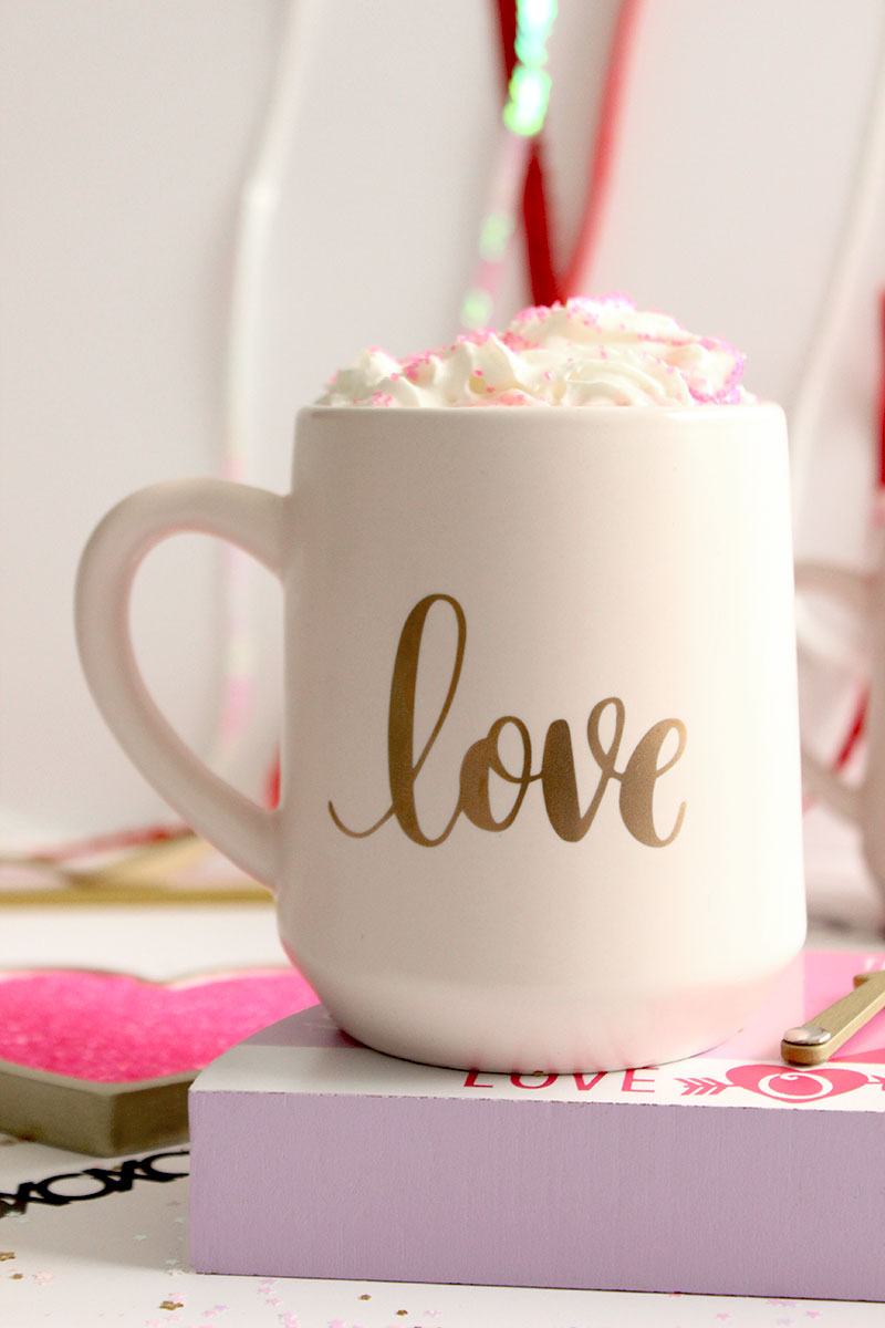 A cute love mug filled with white hot chocolate.