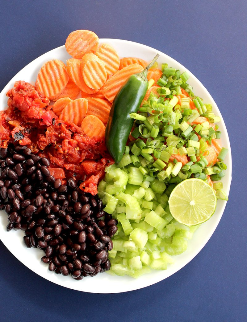 A plate of vegetable sits on a blue background waiting to be put into a delicious Southwest Soup.