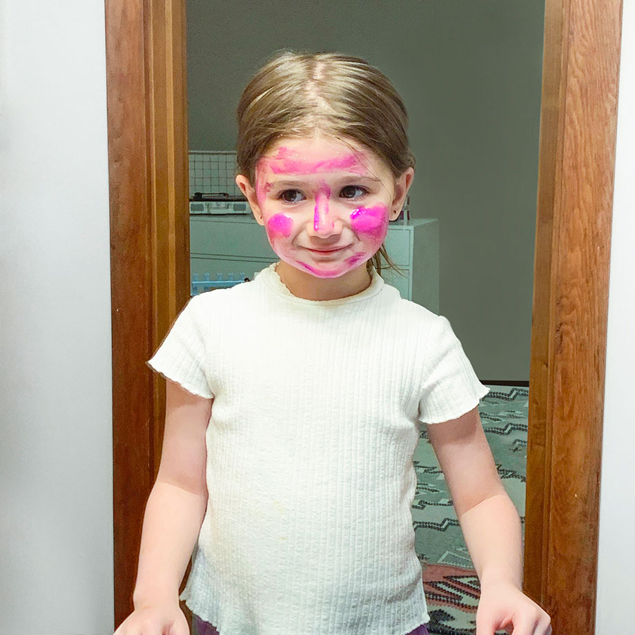 Zelda of Glitter and Bubbles paints her face pink.