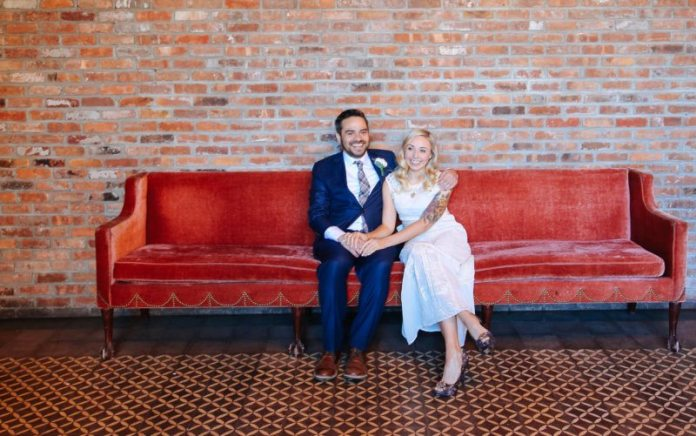 bride and groom sitting on red couch nyc Bowrey