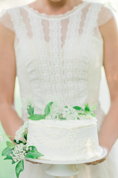 bride holding white cake with green leaves