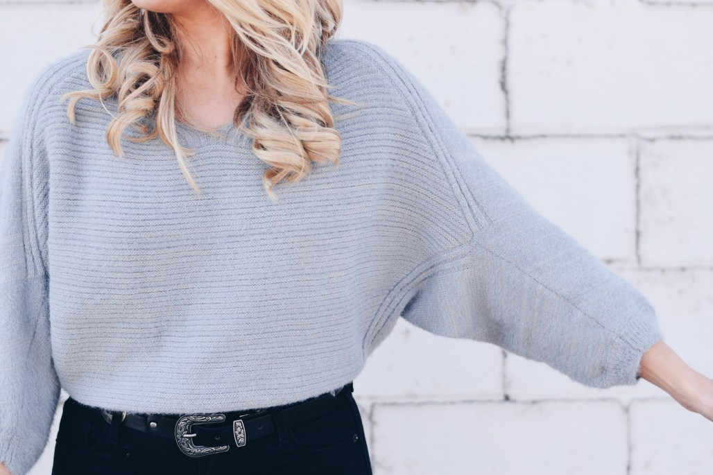 grey fuzzy batwing sleeve sweater with black jeans and western belt