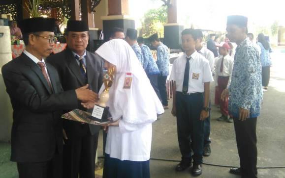 GN/Masdawi Dahlan Khalil Asyari didampingi Tarsun menyerahkan hadiah pada guru dan siswa berprestasi.