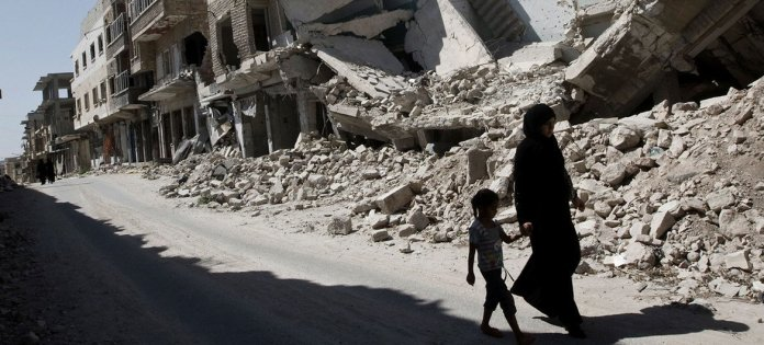 A young girl and a woman walk past destroyed buildings in the city of Maarat al-Numaan in Idlib, Syria.