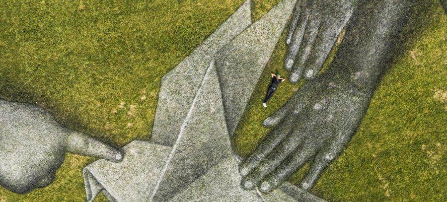 Swiss-French artist Saype (Guillaume Legros) poses in his giant ephemeral landart painting.