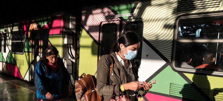 Dos mujeres en el tren de la Ciudad de México se protegen del coronavirus con mascarillas.
