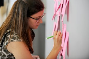 A young person writing on a postit.