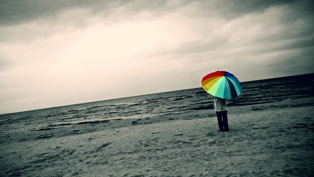 A moody photo of a person with a beach umbrella