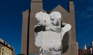 A mural featuring two men hugging