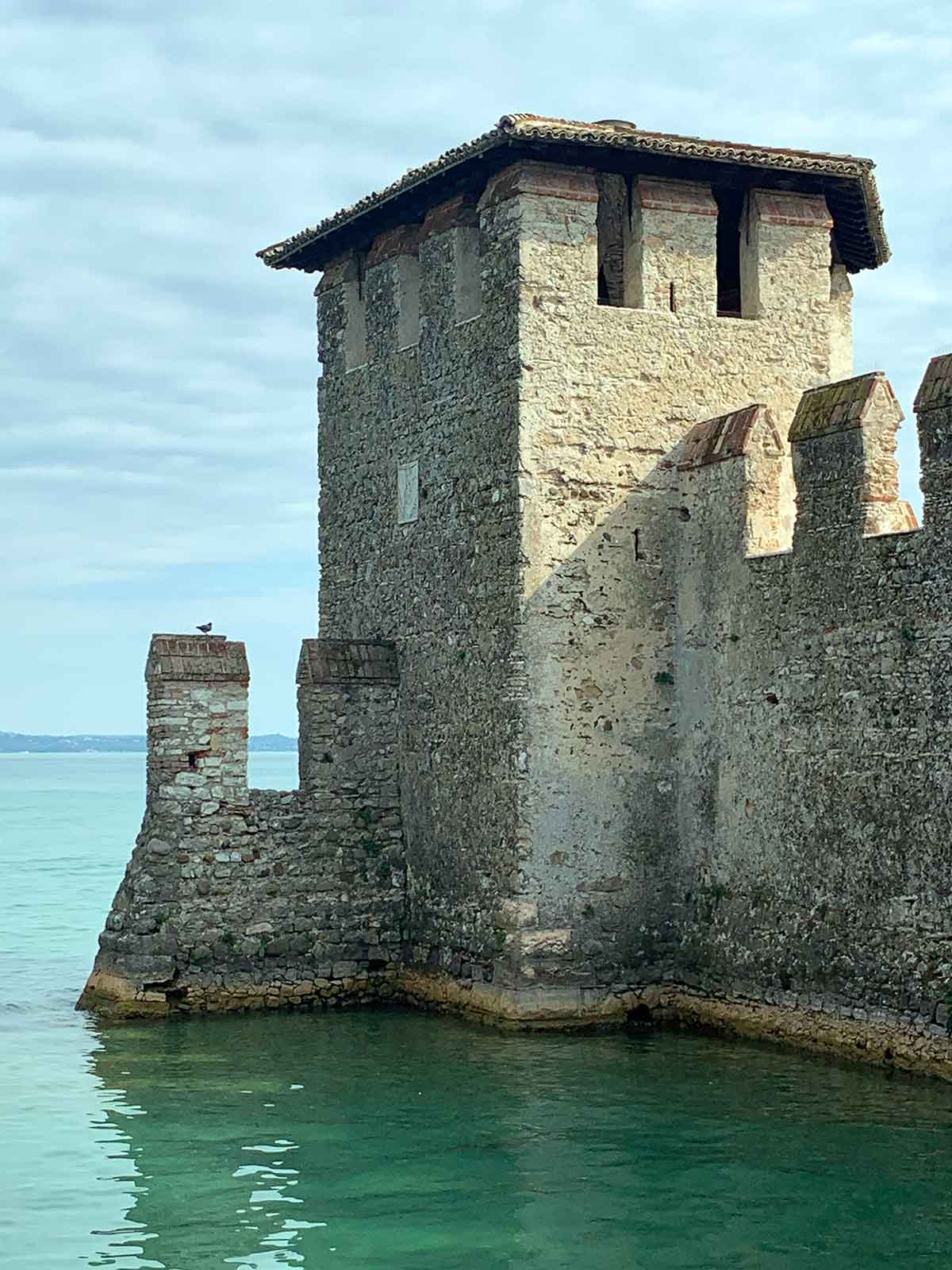 Bird on a tower of Sirmione Castle in Lake Garda, Italy