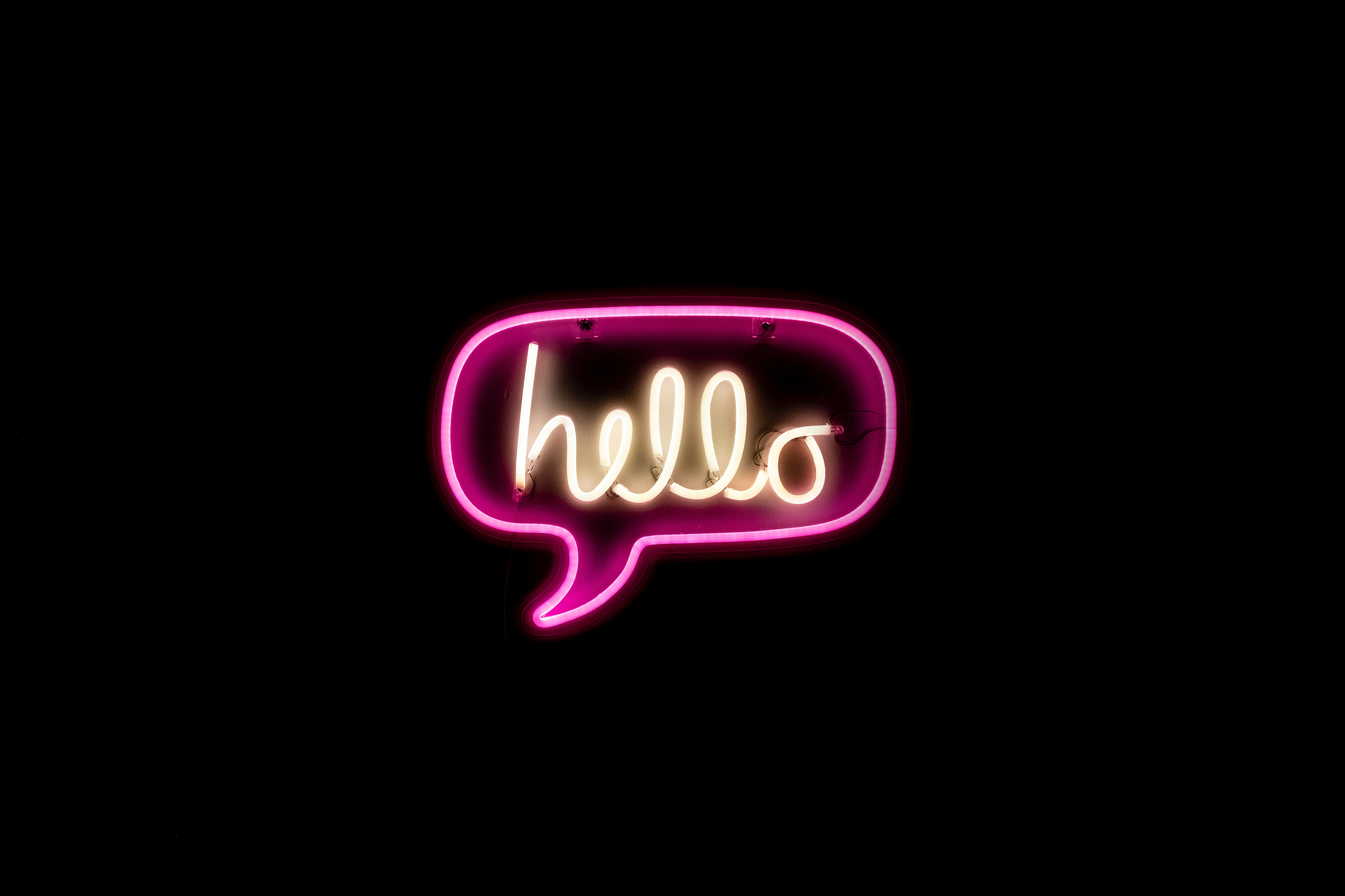 """A neon sign with hot pink and white neon reads """"hello"""" in playful cursive script on a black background"""