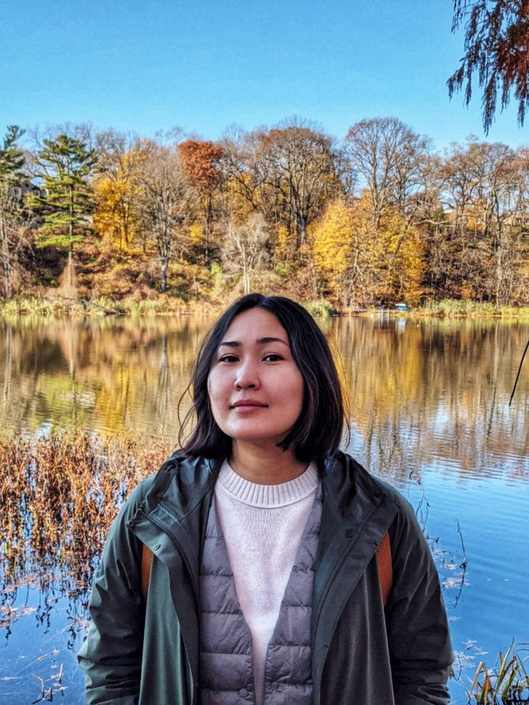 A picture of Gyuzel outside by a lake on a sunny Fall day. She has brown straight mid-length hair. She wears a green parka over a white sweater and a grey jacket. Her head is turned slightly to the left.