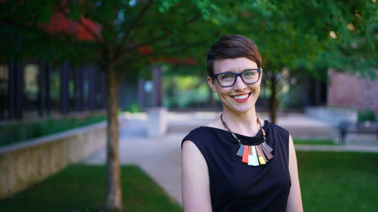 a white woman with short brown hair and glasses, wearing a black dress and colorful necklace, smiles at the camera. She stands on grass, under a tree, in front of a building of brick and glass.